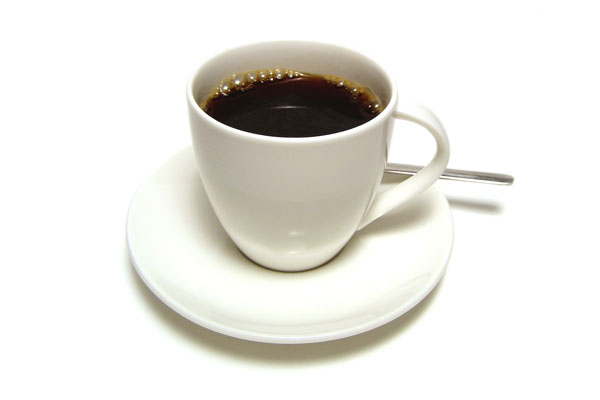 Coffee cup on a saucer with a spoon on white background