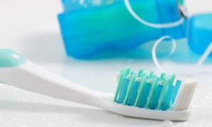 Close up of white toothbrush with blue and green bristles