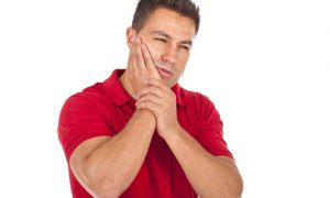 man holds his jaw in pain from toothache