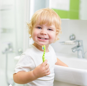 smiling toddler holding toothbrush in front of sink
