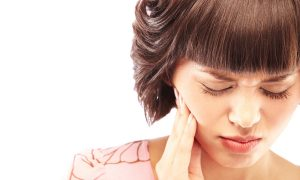 woman holding side of face in pain