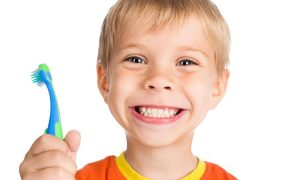boy smiling holding a blue and green toothbrush